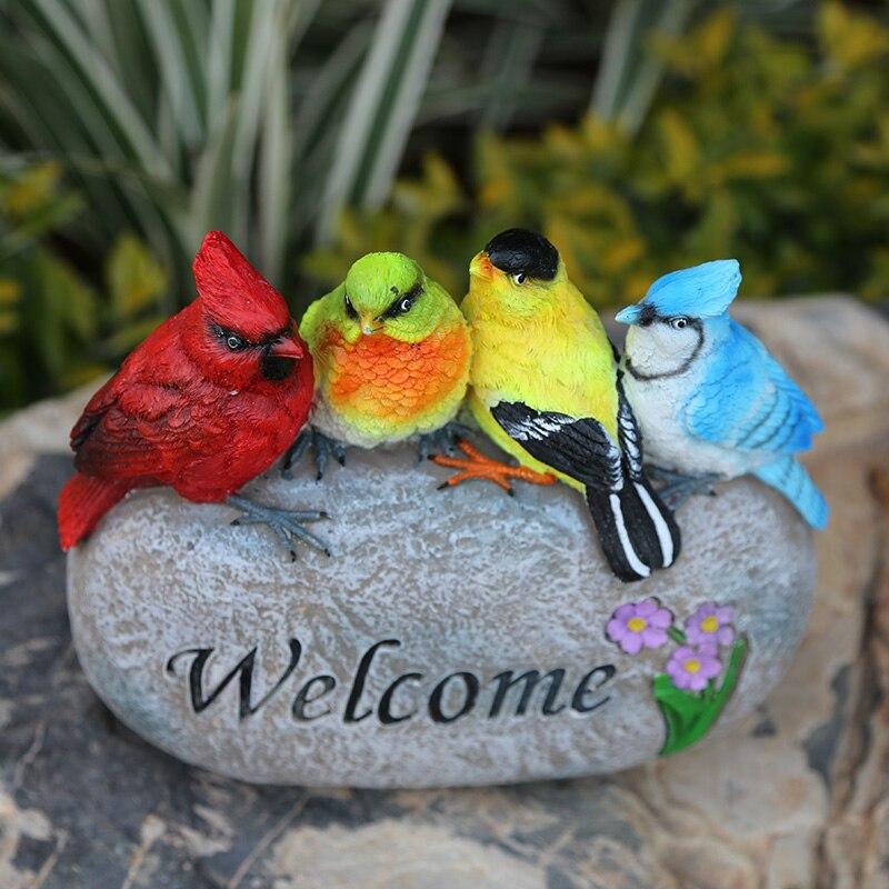 الطيور الملونة الدائمة على حجر الرف مع علامات لويحات ترحيب الراتنج