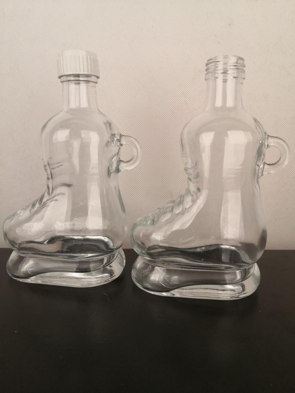 Bouteille en verre de verrerie de forme de patinage de forme de botte avec le couvercle vissable