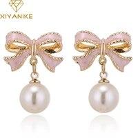 xiyanike sweet lovely gold color pink enamel butterfly bow knot imitate pearl drop earrings for women boucle doreille brin e897