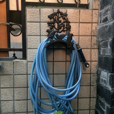 Colgador de manguera de jardín de hierro fundido montado en la pared, estante con adorno de pájaro y diseño de rama de árbol
