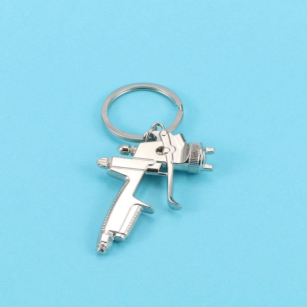 Llavero original de Metal para pistola de agua, 1 Uds., novedad, llavero pequeño con pistola pulverizadora de agua, accesorios para bolsos