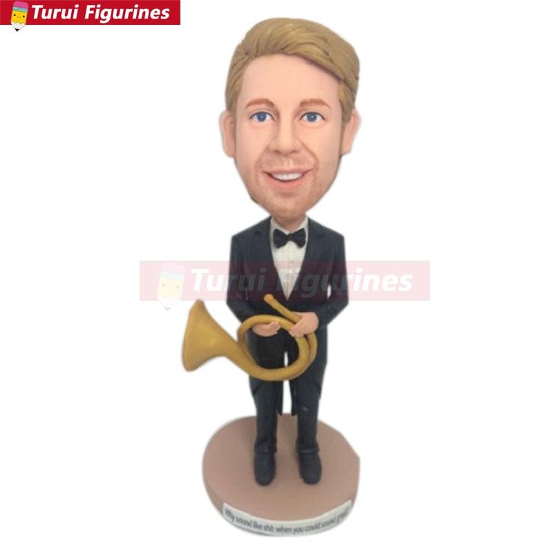 El jugador de cuerno personaliza las figuritas de arcilla de regalo basadas en las fotos de los clientes usando como adorno de pastel de cumpleaños el hijo novio del marido Vale