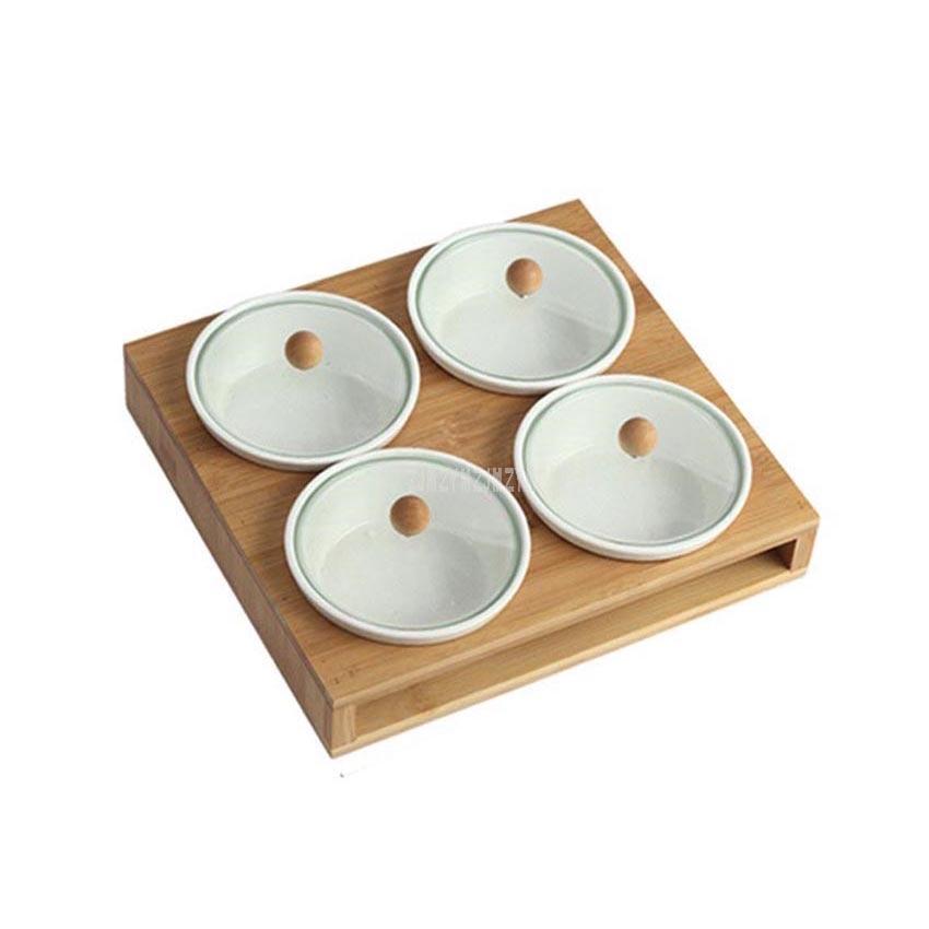 طقم أواني مطبخ بيضاء بسيطة ، برطمانات لتوابل الملح والفلفل ، سيراميك ، إطار من الخيزران ، أدوات مطبخ معلقة على الحائط