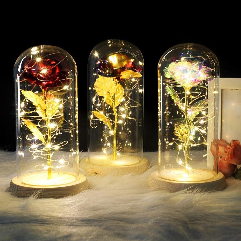 Em uma cúpula de vidro há uma rosa vermelha e rosa colorida besta em uma base de madeira para o dia dos namorados rosa luzes de natal led